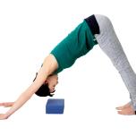 ダウンドッグの姿勢になり、体の下にブロックを置く。ブロックをセットする位置は、手と足の真ん中よりもやや前方。