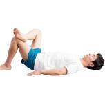 右のポーズの軽減ポーズ。仰向けで膝を立て、両手を体の横に置く。右膝を曲げ、足首を左膝の上にのせる。ここまででもOK。
