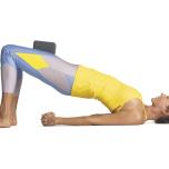 太腿でブロックをはさんでみよう。両足を平行にして腰幅に開き、ブロックのいちばん薄い面を太腿ではさむ。ブロックを両側から押しながら、体を引き上げてブリッジポーズに入る。こうすると、膝が開かず、お尻が硬く