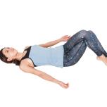 仰向けになって膝を立て、左脚を上からひっかけて脚を組む。両手はラクな位置に置き、脚を右方向に倒していく。