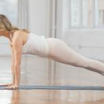 ダウンドッグの姿勢から、かかとを後ろに引いて上体を前に出し、手首の真上に肩がくるように調整する。手のひらでマットを押しながら、腕から上に引き上げるようにする。肋骨の下部を背骨のほうに引き込み、鎖骨を左