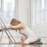 椅子に向かって座り、足を左右に開く。太腿上部でマットを押して足を活性させ、股関節から前屈し、上体を椅子に向かって長く伸ばす。椅子の座面に置いた1~2枚のブランケットの上に額を休ませ、肘を曲げて手を座面