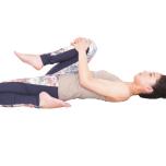 右膝を胸に引き寄せて10秒キープ。ひとつ前のストレッチからここまでを、反対側も。痛みを感じず、ラクに呼吸できる範囲で行う。