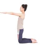 膝立ちになり、足の甲を床につける。両腕を体の前で肩の高さに上げ、手のひらを下に。