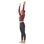 両足を手に向かって歩かせたら、そのままマットの前方でロールアップしてターダーサナ(山のポーズ)に入る。腰の真下に足がくるように調整し、手は体の横に。息を吸って両腕を横に広げながら頭上に伸ばし、手のひら