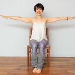 両手を肩の高さまで上げ、左右に大きく開く。両脚は揃えたまま、腹筋を使って床から少し持ち上げて浮かせる。