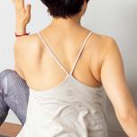 息を吐いて上体をねじったところ。肩まわりがすくみやすいので、胸と鎖骨を広げて、胸を広く保つ。